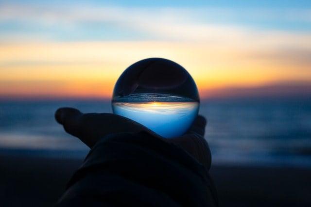 main-tenant-une-boule-de-cristal-en-bord-de-plage-avec-couche-de-soleil